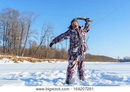 Bearded man is trying to slam you by frozen fish after successful winter fishing at cold sunny day under clear blue sky
