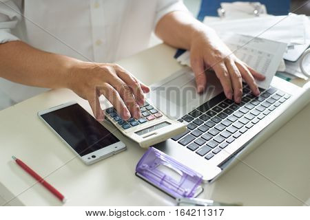 Business men work with calculator and laptop on the white table at office