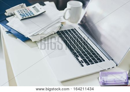 Cup of coffee documents and laptop on the table of business person