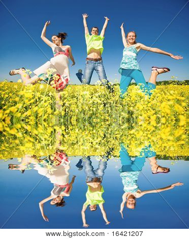 Happy people are jumping, having fun on the river bank. The reflection in the water.
