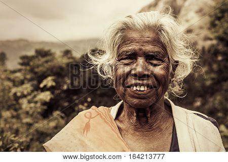 Old smiling indian woman. Elderly wrinkles. White hair and worn teeth. Location: Ella, Sri Lanka. July 2016
