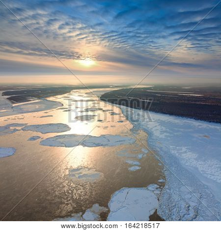 Aerial view great river with spring debacle during sundown. Floating of ice.
