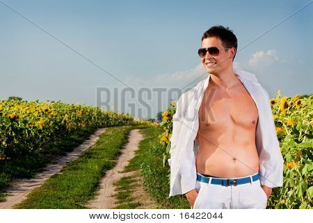 Happy young man in a field of sunflowers