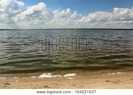 Beautiful landscape of the sea coast with yellow sand, waves, blue sky with white clouds.