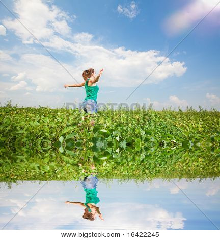Beautiful young woman on a green meadow. Specular reflection in the water.