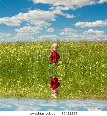 Happy boy enjoy on the meadow. Specular reflection in the water.