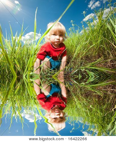 Happy boy enjoy on the meadow. Specular reflection in water
