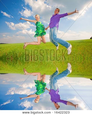 Happy people is jumping in field. Specular reflection in the water.