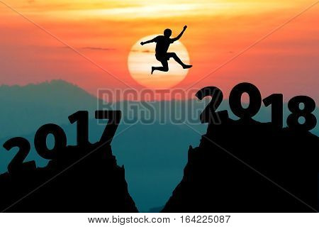 A man jump between 2017 and 2018 years. HAPPY NEW YEAR GOAL concept