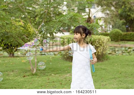 7 years old black hair Asian girl in white dress play and enjoy with soap bubbles balloon in park
