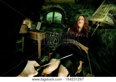 young woman tied to a chair in a dirty cellar