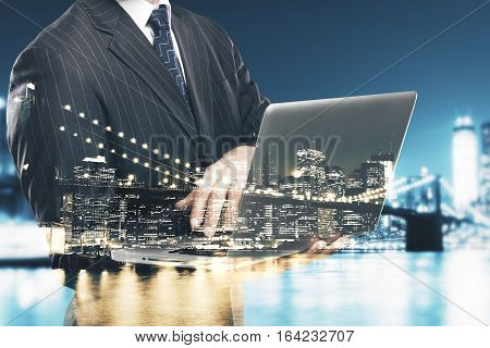 Abstract image of caucasian businessman using laptop on city background. Double exposure. Communication concept