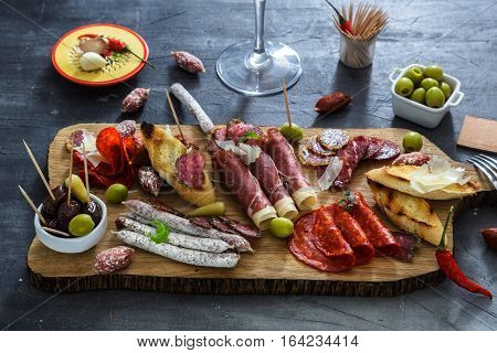 Mix of different snacks and appetizers. Spanish tapas on a black stone background. Tapas bar. Space for text. Deli, sandwiches, olives, sausage, anchovies, cheese, jamon, pepper, tomatoes Top view