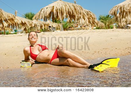 girl in red bikini with mask and flippers on beach