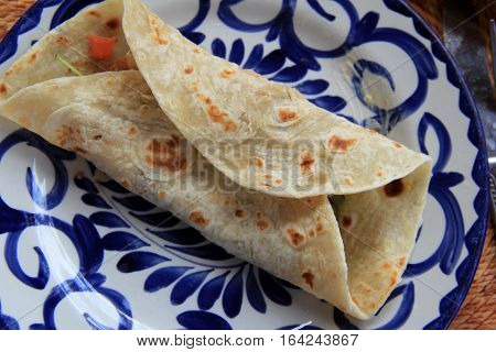 Colorful blue and white plate with soft tortilla