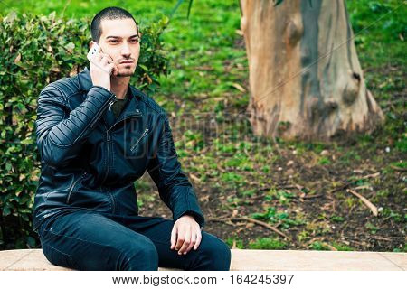 Young man with smartphone. Talking on the phone. A young and handsome boy is talking on the phone with someone. His mood is serious. Outdoors in a park.