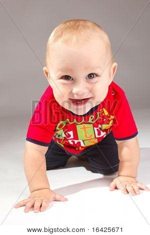 Lachend Kleinkind krabbelt über grau