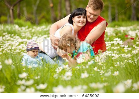 Preschool girl smelling flowers, her family looking at her