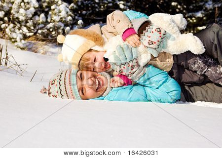 Happy mother and little girl lying in snow