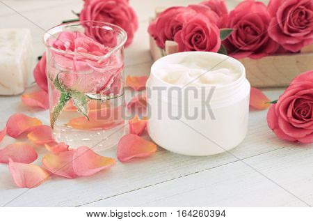Jar of facial anti-age cream, infused floral attar in glass test vial, fresh roses, pink petals, white wooden table. Soft focus, toned.