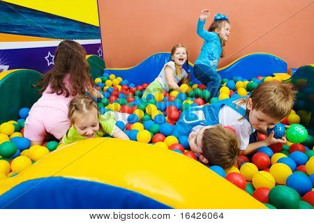 Joyful kids playing in the pool with colorful balls