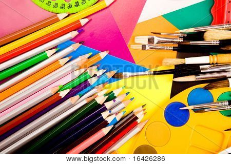Colorful art supplies lying on cardboard