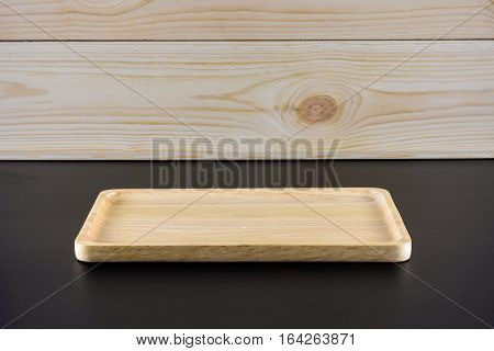 Blank wood plate on black table and wood background
