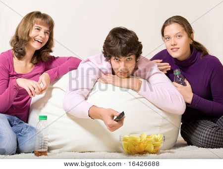 Three cheerful teenage friends watching TV and having snack