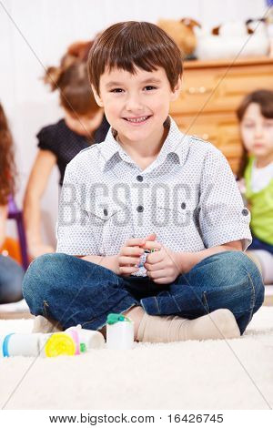Handsome preschool boy playing with dough in the kindergarten
