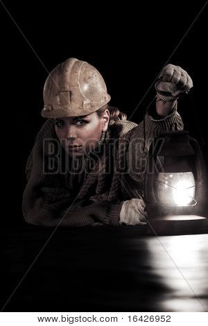 Beautiful young woman in hardhat with oil stove