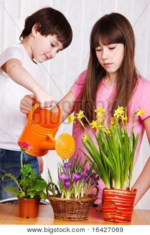 Two cute kids watering flowers