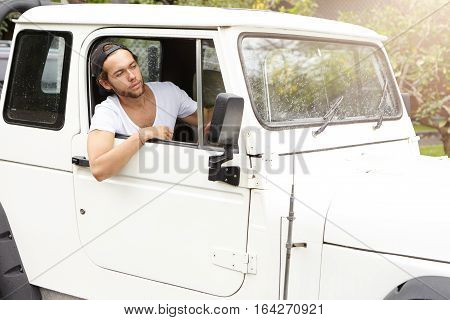 Adventure, Leisure And Travel Concept. Young Man In T-shirt And Snapback Sitting Inside His White Je