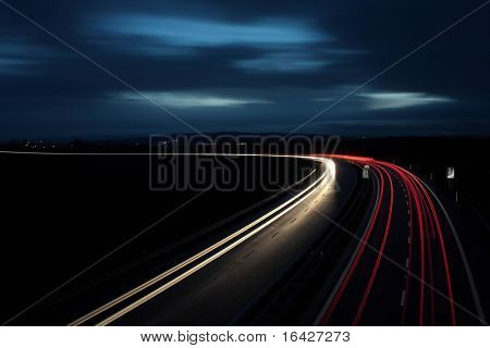 Cars moving fast on a highway.