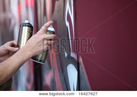 Graffiti Artist hands with paint cans