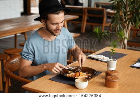 Portrait Of Handsome Young Man With Beard Smiling Happily As He Eating Some Tasty Food With Knife An