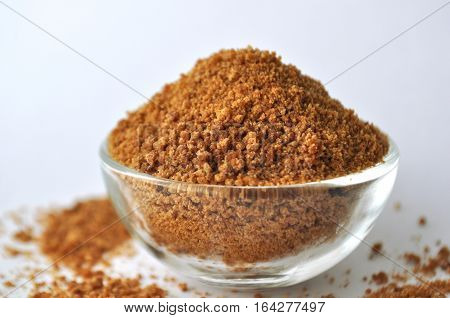 Organic coconut sugar - alternative sweetener in a glass bowl on white