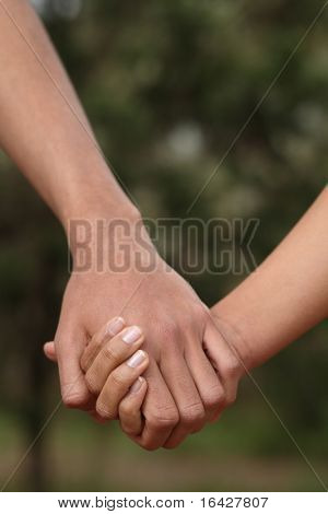 Young couple holding hands (closeup)