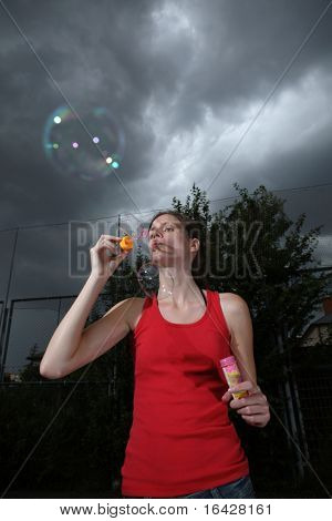 Pretty young woman blowing soap bubbles against dramatic stormy sky