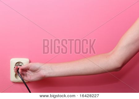 Young woman's hand plugging a power plug into an electric wall socket at a pink wall