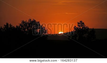 An amazing sunset over the trees and mountains rich orange hue