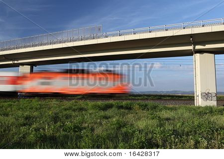 Fast train passing under a bridge on a lovely summer day (motion blurred image)