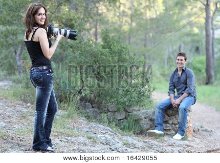 Female photographer takes pictures of a great looking male model on location outdoors