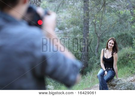 Young photographer takes pictures of a great looking female model on location outdoors