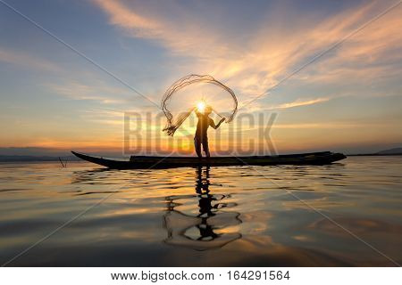 Silhouette of asian fisherman on wooden boat fisherman in action catching freshwater fish in nature river traditional fishermen at the sunset near Inle lakeMyanmar