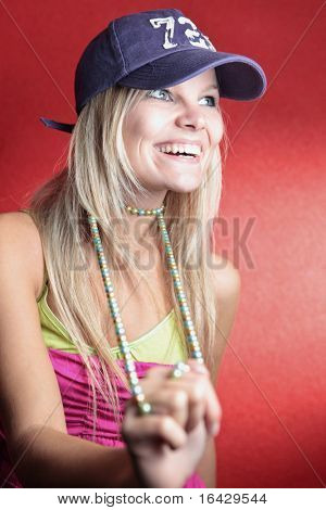 Portrait of a beautiful young blonde woman wearing a baseball cap and a necklace posing in front of a red wall