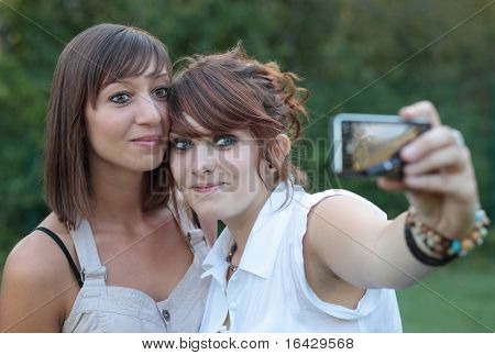 two young caucasian female friends taking autoportraits of themselves having fun while outdoors in a park