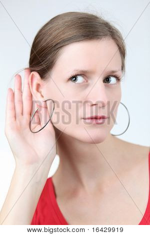 Pretty young woman puts her hand to her ear and listens attentively