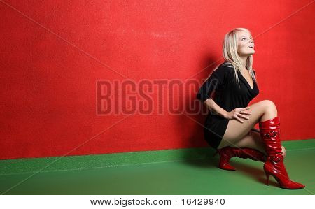 Beautiful young female photo model wearing high red boots posing in front of a red wall