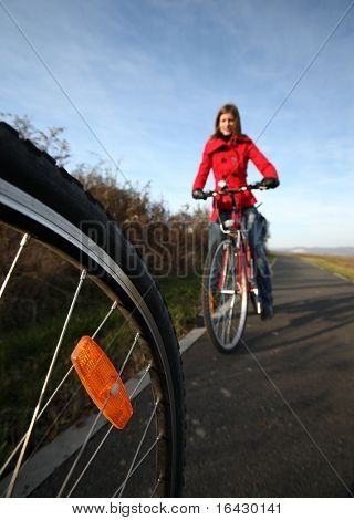 Biking (the image is motion blurred to convey movement; focus is on the wheel, the female biker is left out of focus)