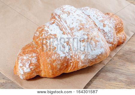 Fresh Croissant with powdered sugar. Baked Tasty croissants on old wooden background